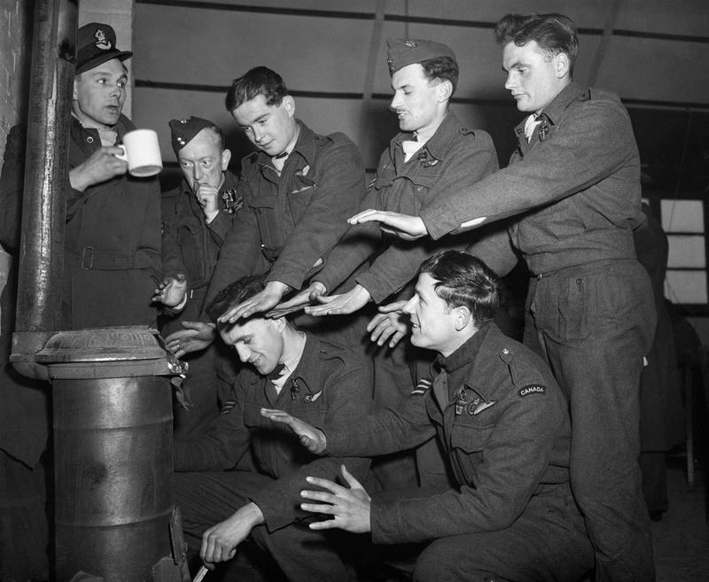 "The crew of Lancaster ""C for Charlie"" of 44 Squadron try to warm themselves in their Nissen hut quarters at Dunholme Lodge, 2 March 1944 (c. Imperial War Museum)"